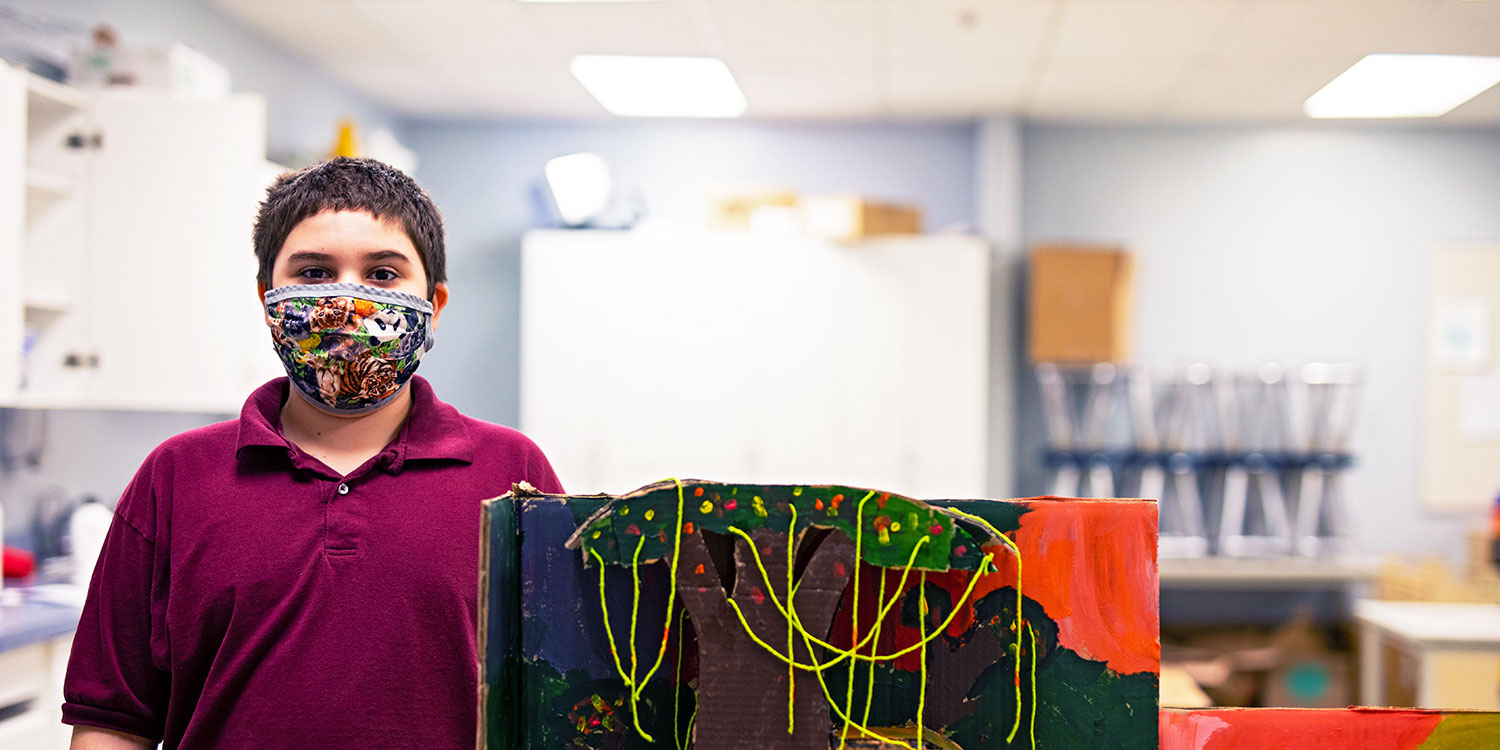 Masked student standing next to diorama.