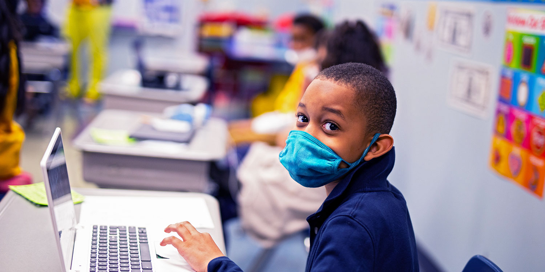 Masked elementary student working on laptop.