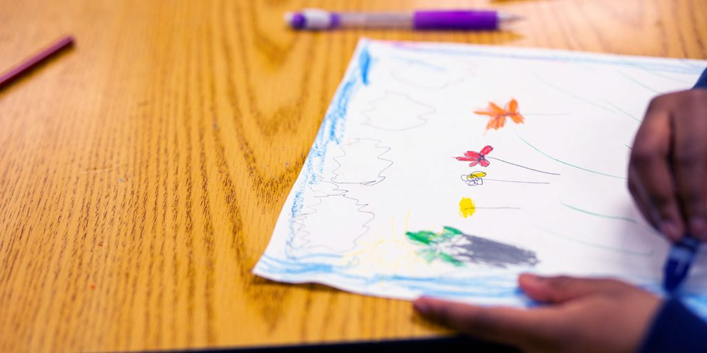 Student drawing and coloring a picture of flowers.