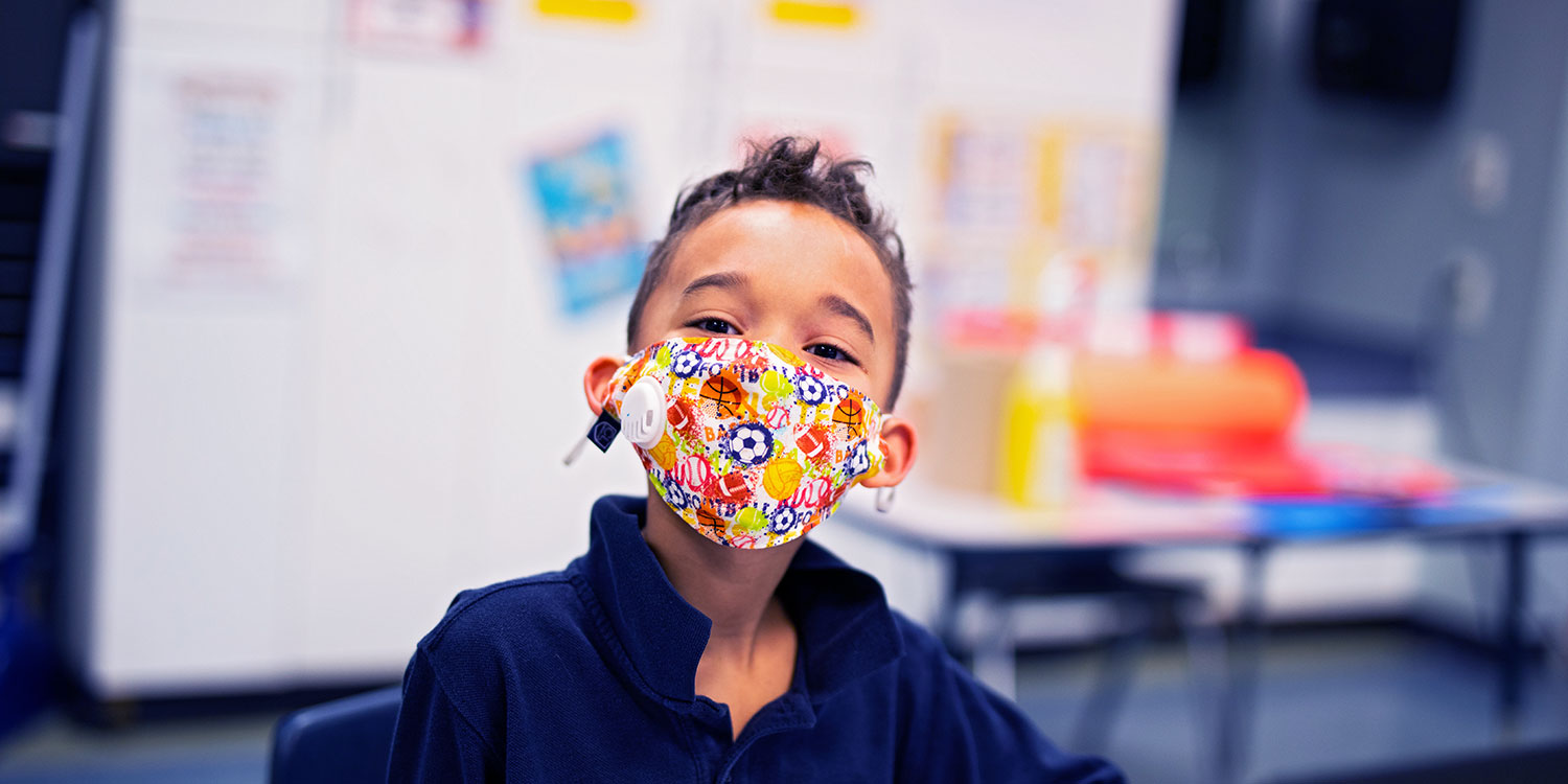 Masked elementary student in a classroom.