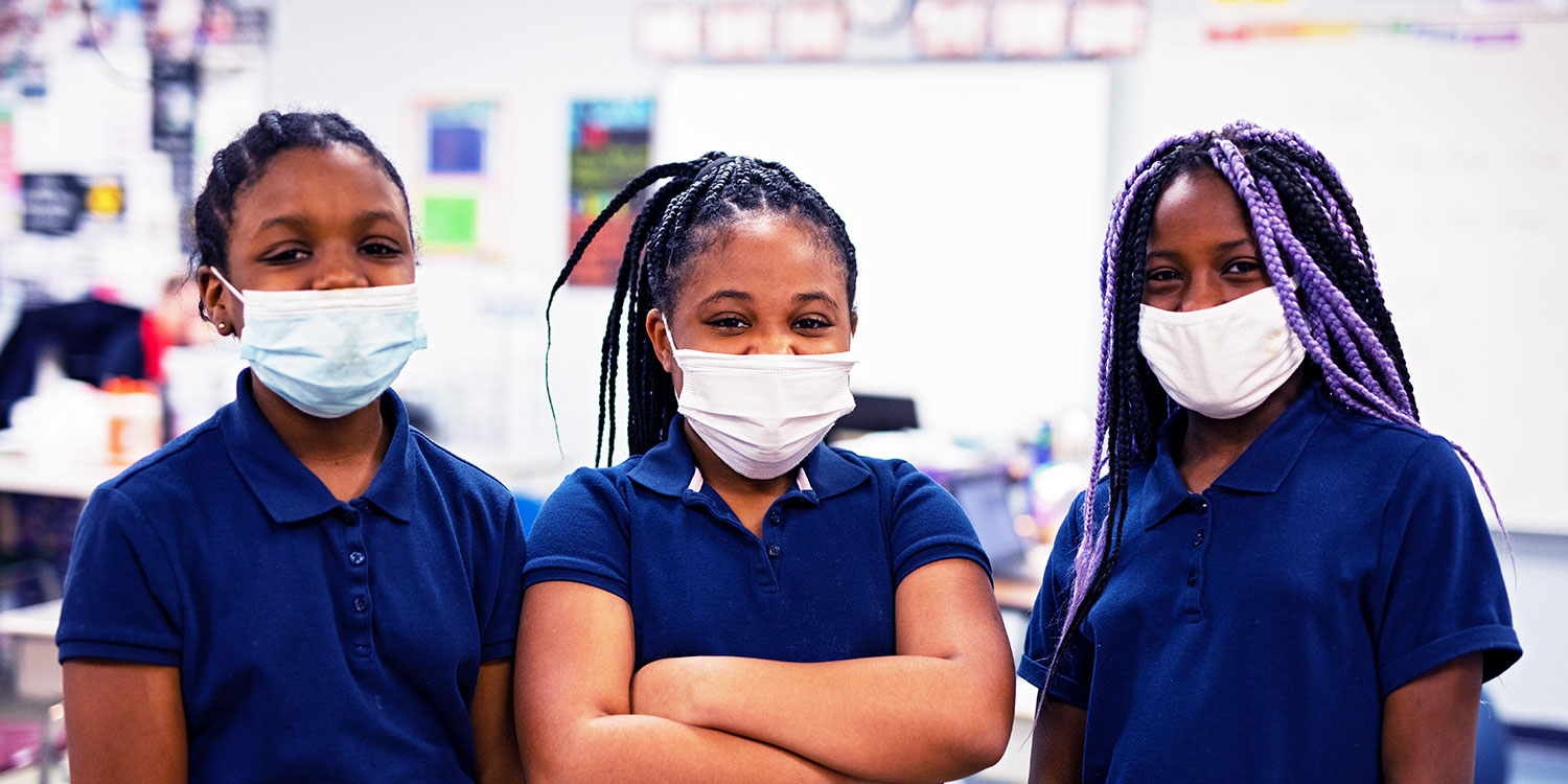 Masked students in a classroom.